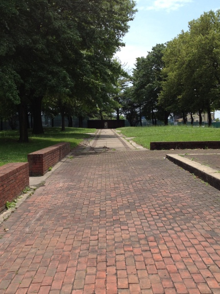 The modest park as seen from the street; the marker is at the end of the brick walkway.